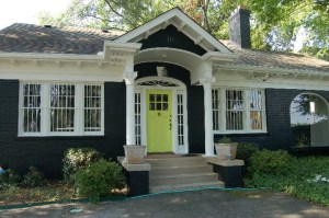 vetted store in atlanta black brick front, white trim, yellow door, imagine light blue shutters